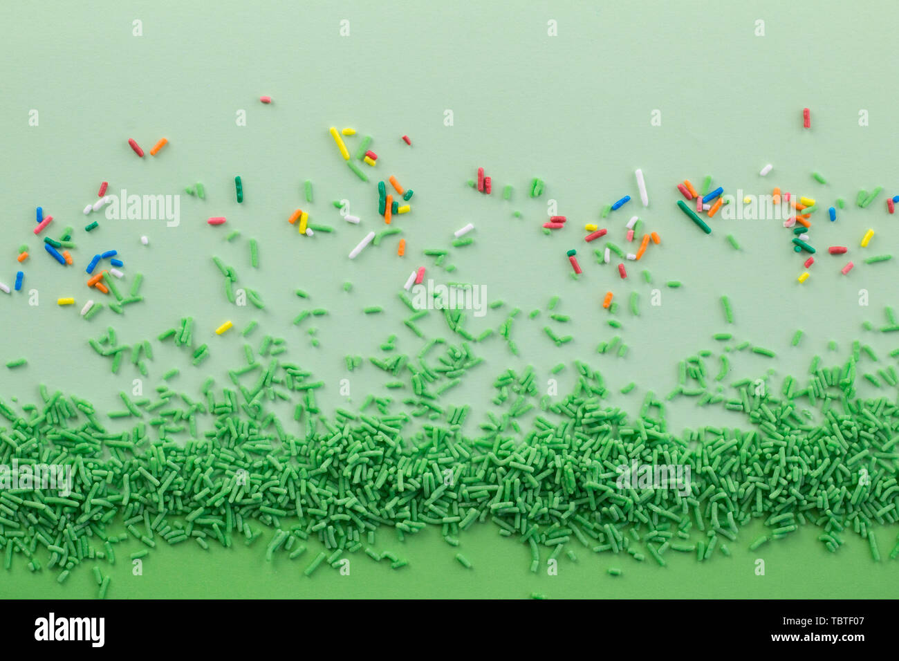 Green sprinkles on two tone green background with multi coloured sprinkles scattered - Cake topping sprinkles green background with space for text - Stock Image
