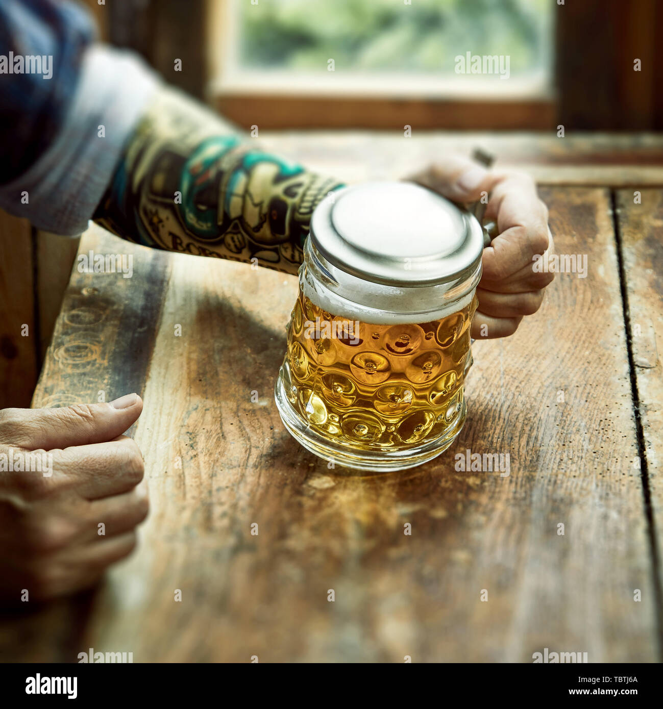 Man With Tattoo On His Arm Seated In A Rustic Tavern With Large Mug Of Beer In A Concept Of Alcoholism Addiction Drunkenness Or Dipsomania Stock Photo Alamy