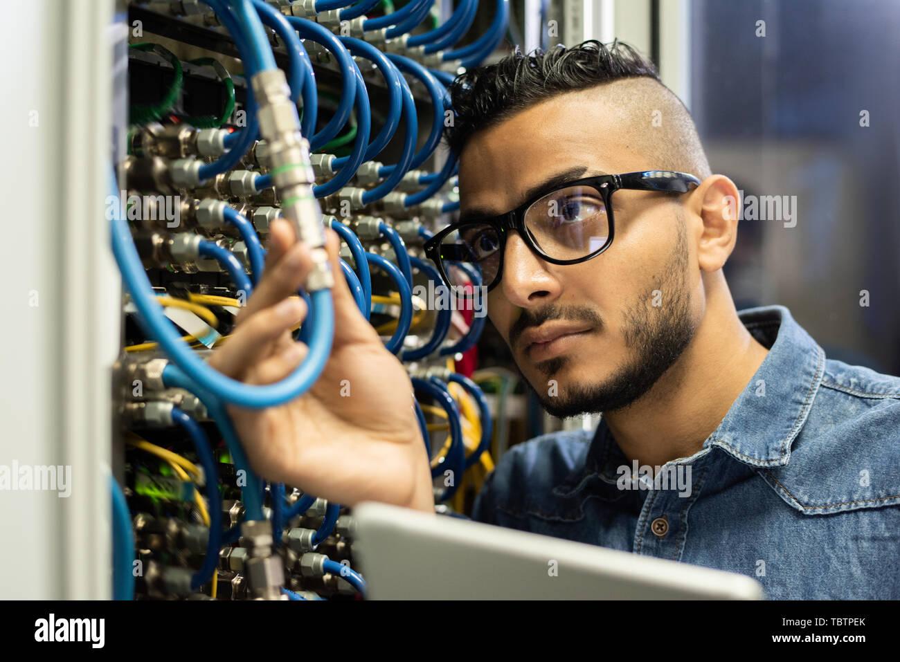 Technical engineer examining mainframe computer - Stock Image