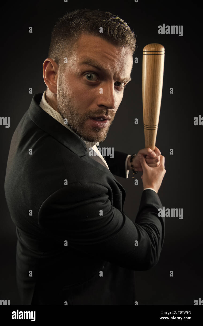 Businessman or man in formal suit on dark background. Man on strict face posing with wooden bat. Man with bristle looks confident and threatening. Aggressive business concept. - Stock Image