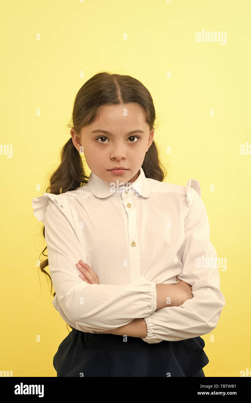 She does not agree with you. Girl serious face offended yellow background. Kid unhappy looks strictly. Girl school uniform folded arms on chest looks serious. Sensitive girl not want to talk. - Stock Image