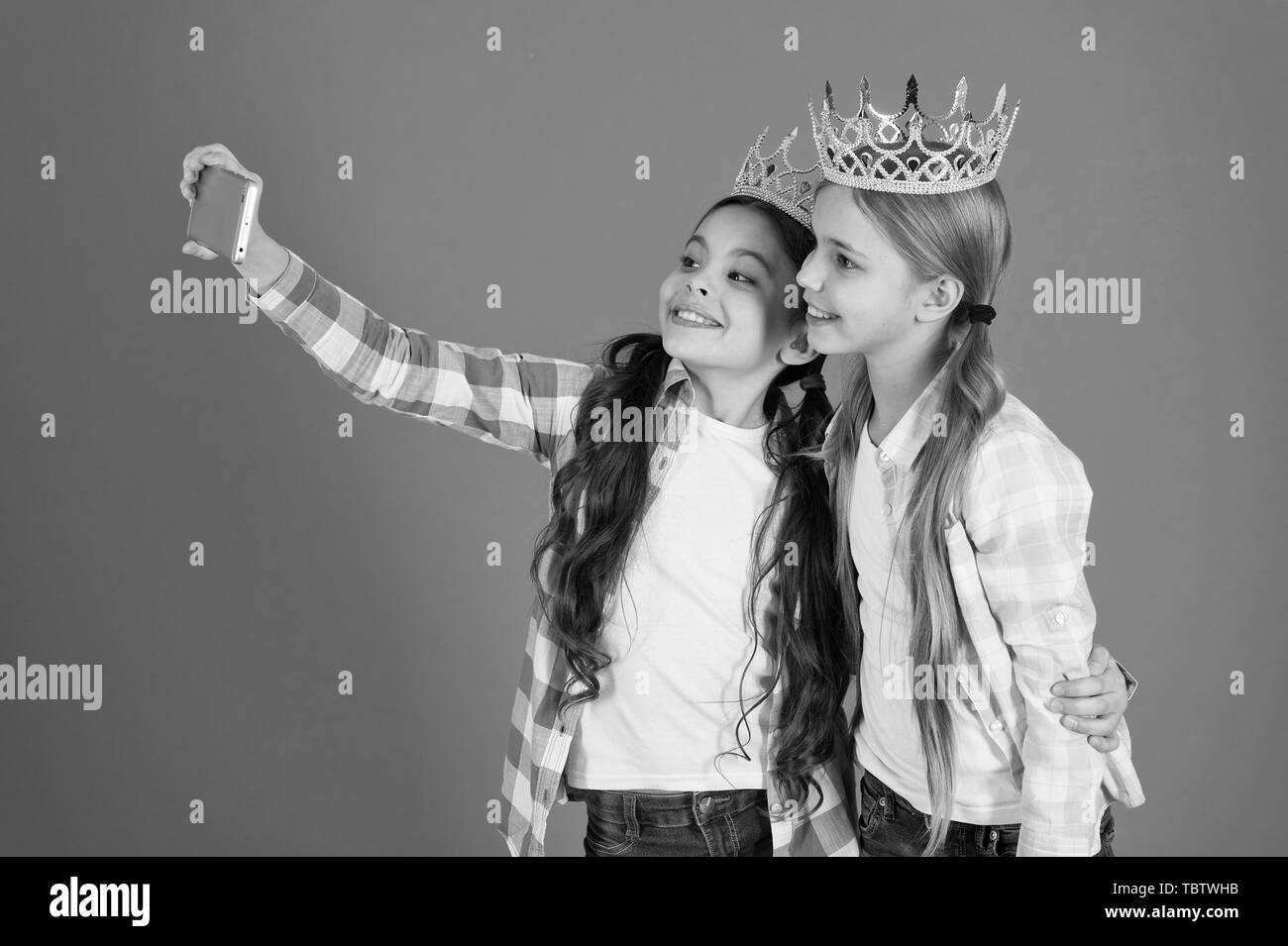 Kids wear golden crowns symbol princess. Warning signs of spoiled child. Avoid raising spoiled kids. Girls taking selfie photo smartphone camera. Spoiled children concept. Demand more attention. - Stock Image