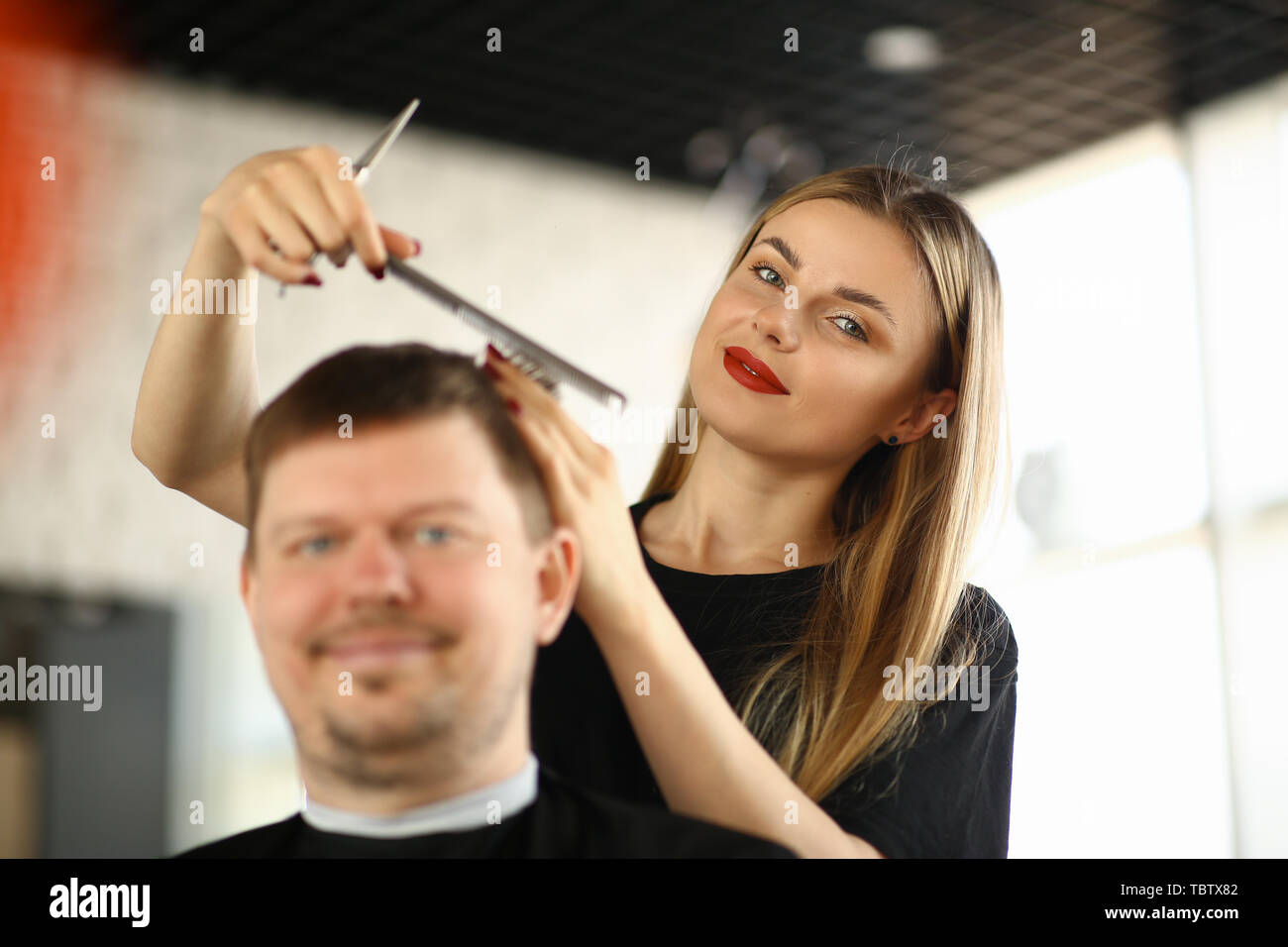 Female Hairdresser Combing Male Client in Salon. Woman Hairstylist Making Hairstyle for Man Sitting in Beauty Studio. Stylist Holding Comb and Scissor Stock Photo