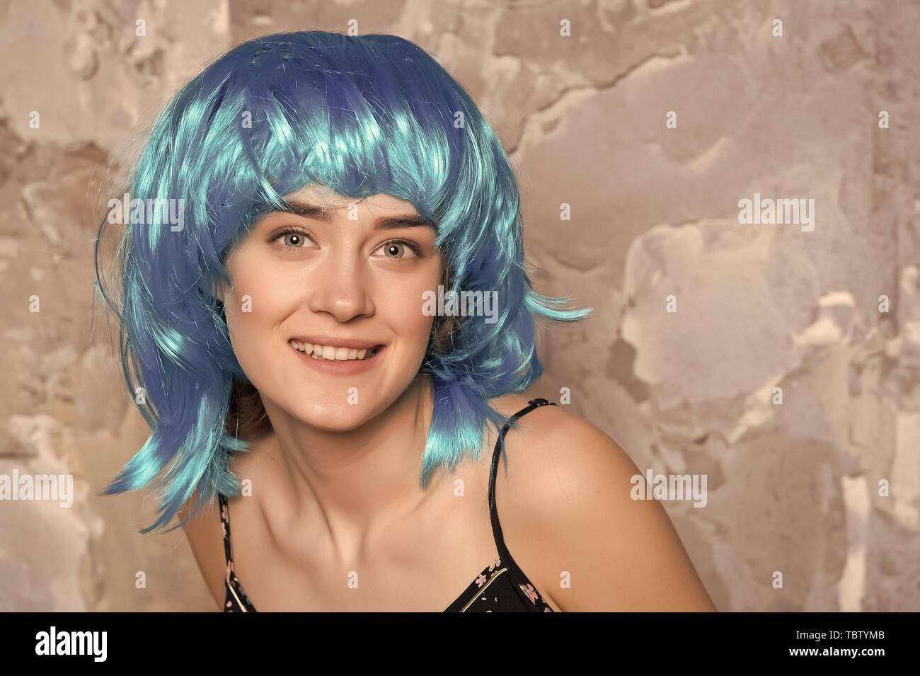 Freak concept. Lady on smiling face posing in blue wig, concrete wall background. Woman with blue hair looks unordinary and extraordinary. Lady freak with unordinary appearance. - Stock Image