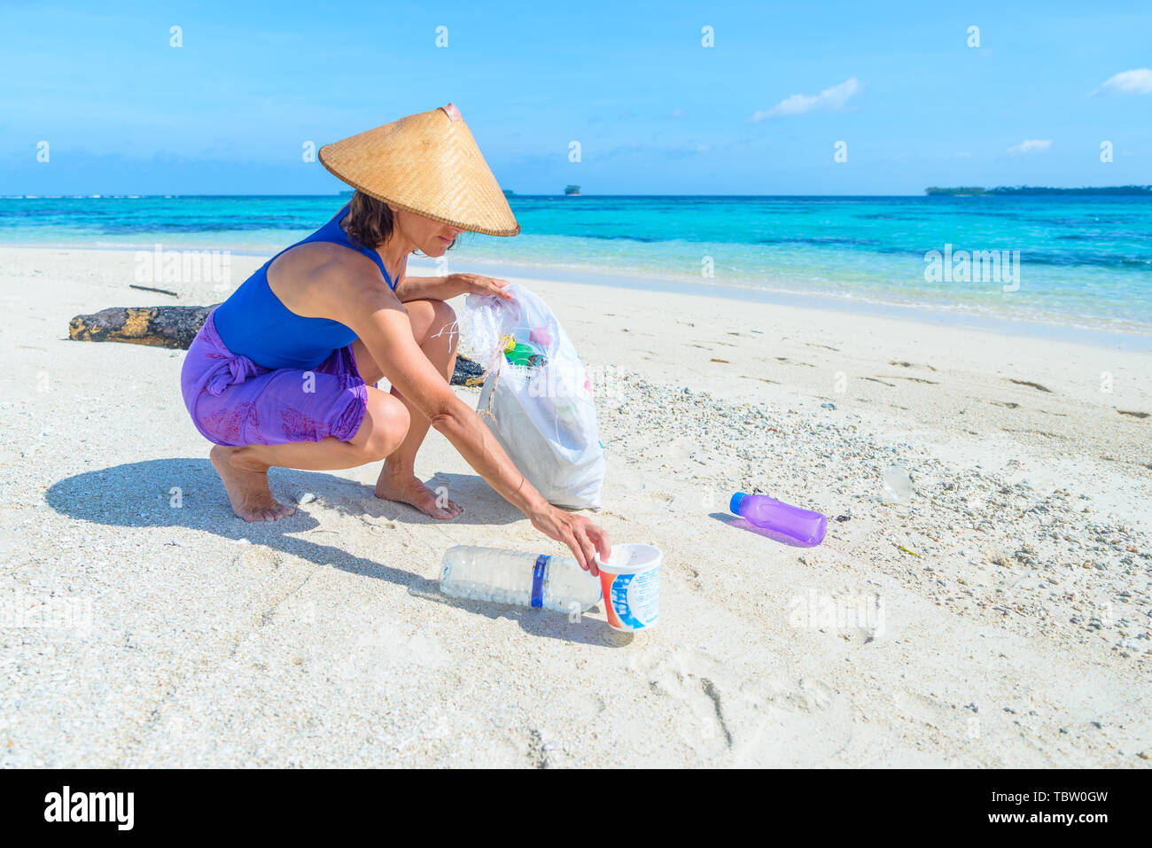 Woman collecting plastic bottles on beautiful tropical beach, turquoise sea, sunny day, recycling rubbish concept, environmental protection. - Stock Image