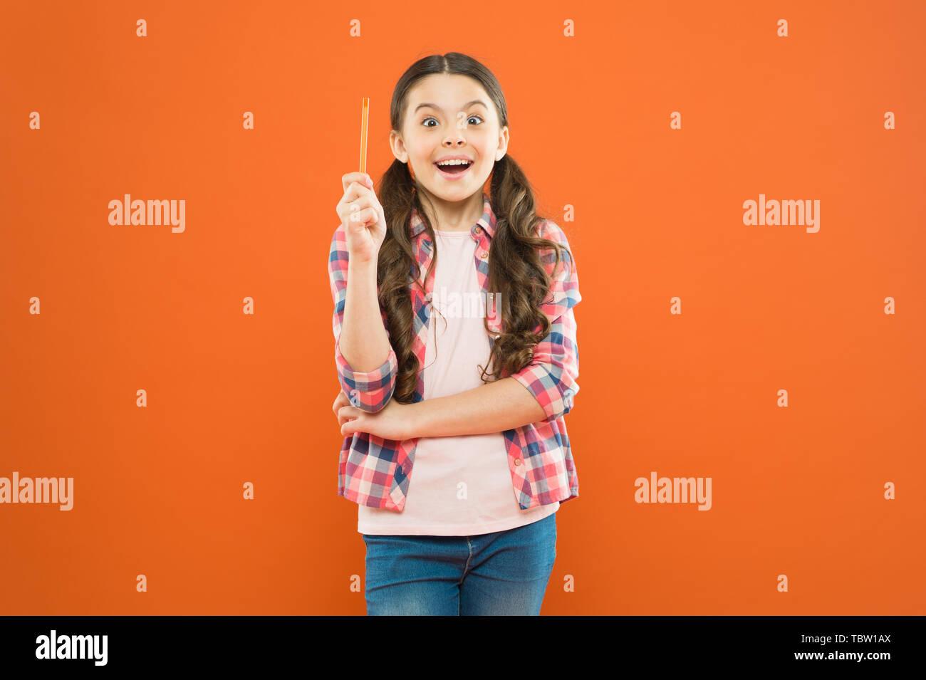 I am the genius. Girl genius. Genius little schoolgirl got a bright idea on orange background. Small child pointing pen up having genius idea. - Stock Image