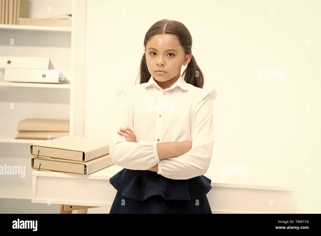Little but serious. Child girl wears school uniform standing with crossed arms on chest. Schoolgirl smart child looks serious white interior background. Girl serious about knowledge and education. - Stock Image