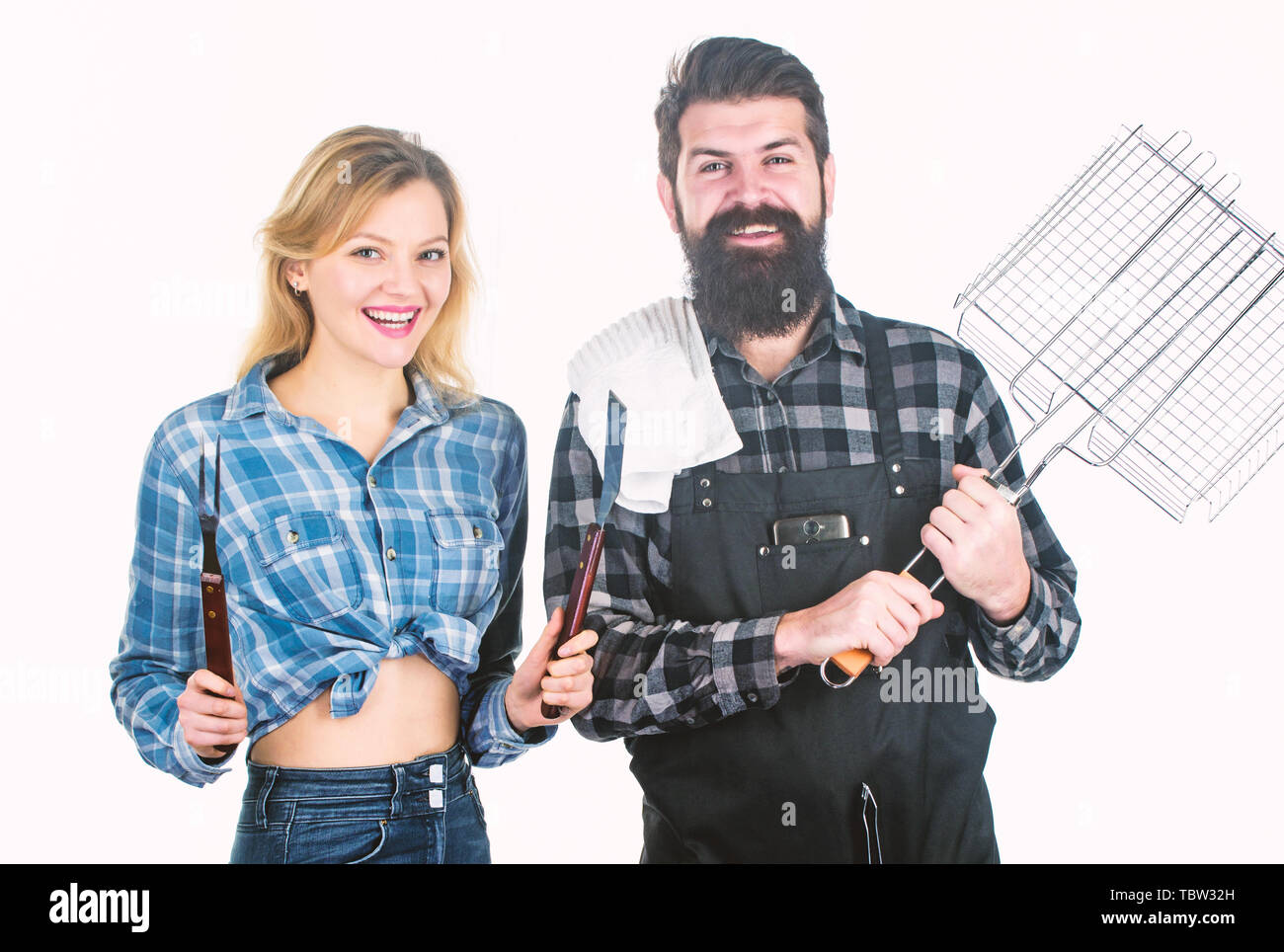 Do it yourself. Having barbecue party. Happy couple ready for cooking barbecue. Man and woman holding barbecue grill. Using barbecue set. - Stock Image