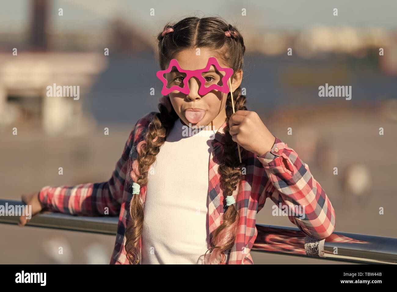 Getting ready for party. Small naughty girl having fun. Fashionable glasses for celebration. Stylish look. Disobedient small girl showing her tounge. Positive moments. Concept of childish carelessness. Stock Photo