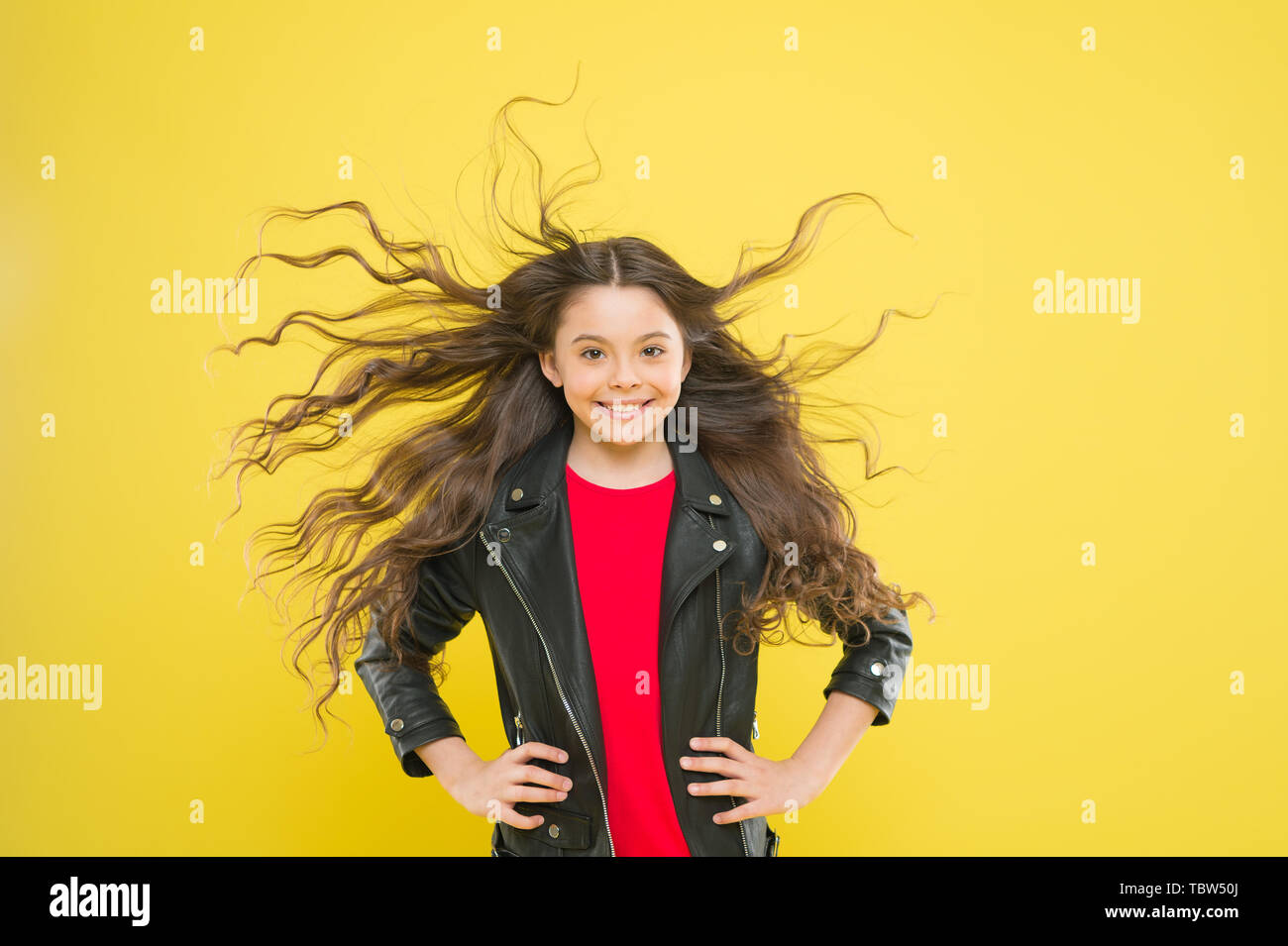 Hairdresser is a girls best friend. Cute little girl with long wavy hair happy smiling on yellow background. Kids hairdresser. Hairdresser salon for children. My hairdresser is good with her hands. - Stock Image