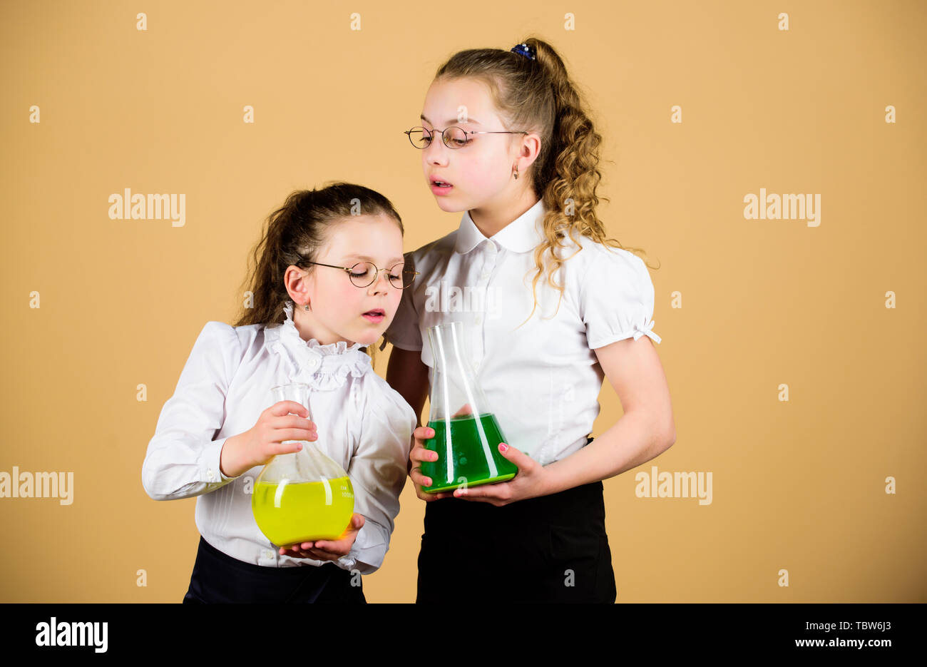 little smart girls with testing flask. back to school. knowledge and education. children study at biology lesson. science research in lab. chemistry flask with liquid. testing flask in hands of kids. - Stock Image