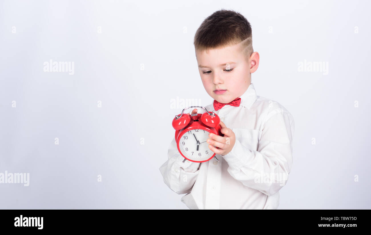 Party time. Businessman. Formal wear. little boy with alarm clock. Time to relax. Time management. Morning. tuxedo kid. Happy childhood. happy child with retro clock in tie. copy space. Just relaxing. - Stock Image