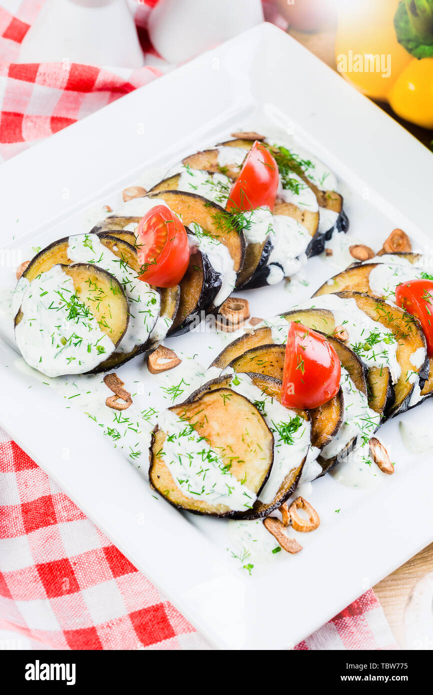 Grilled slices of eggplant and tomatoes in stack with spicy sauce Stock Photo