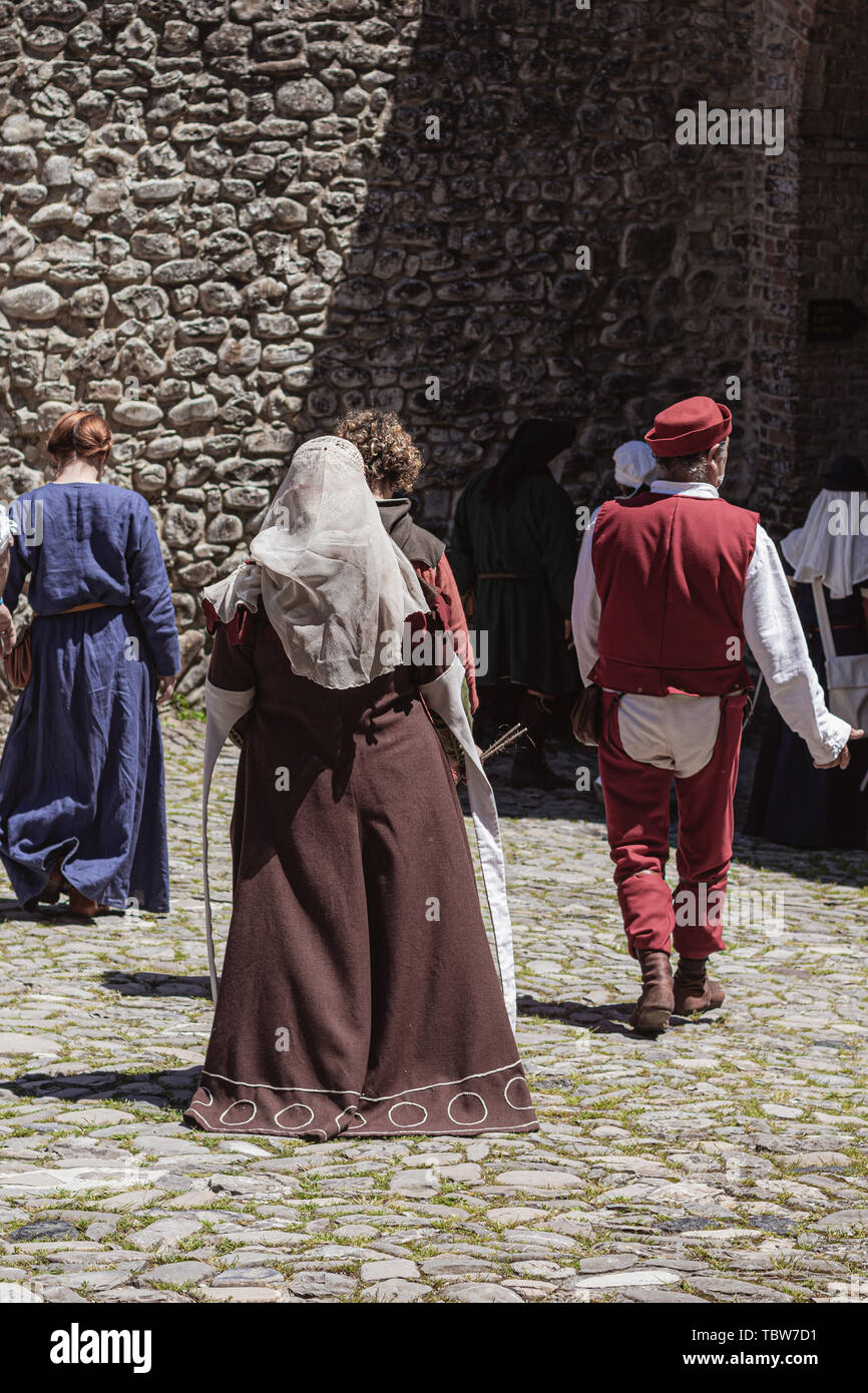 Group of unrecognizable people dressed in medieval costumes walking down an ancient street - Stock Image