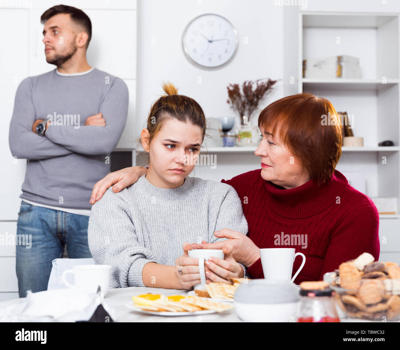 Elderly mother comforting her daughter after discord with husband at home - Stock Image