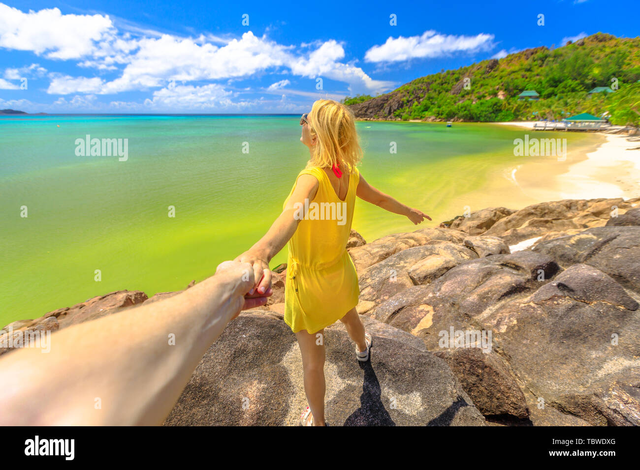 Tropical summer vacations. Follow me. Tourist woman in yellow holding hand of partner at Praslin in Seychelles.Aerial view of Anse Gouvernement with Stock Photo
