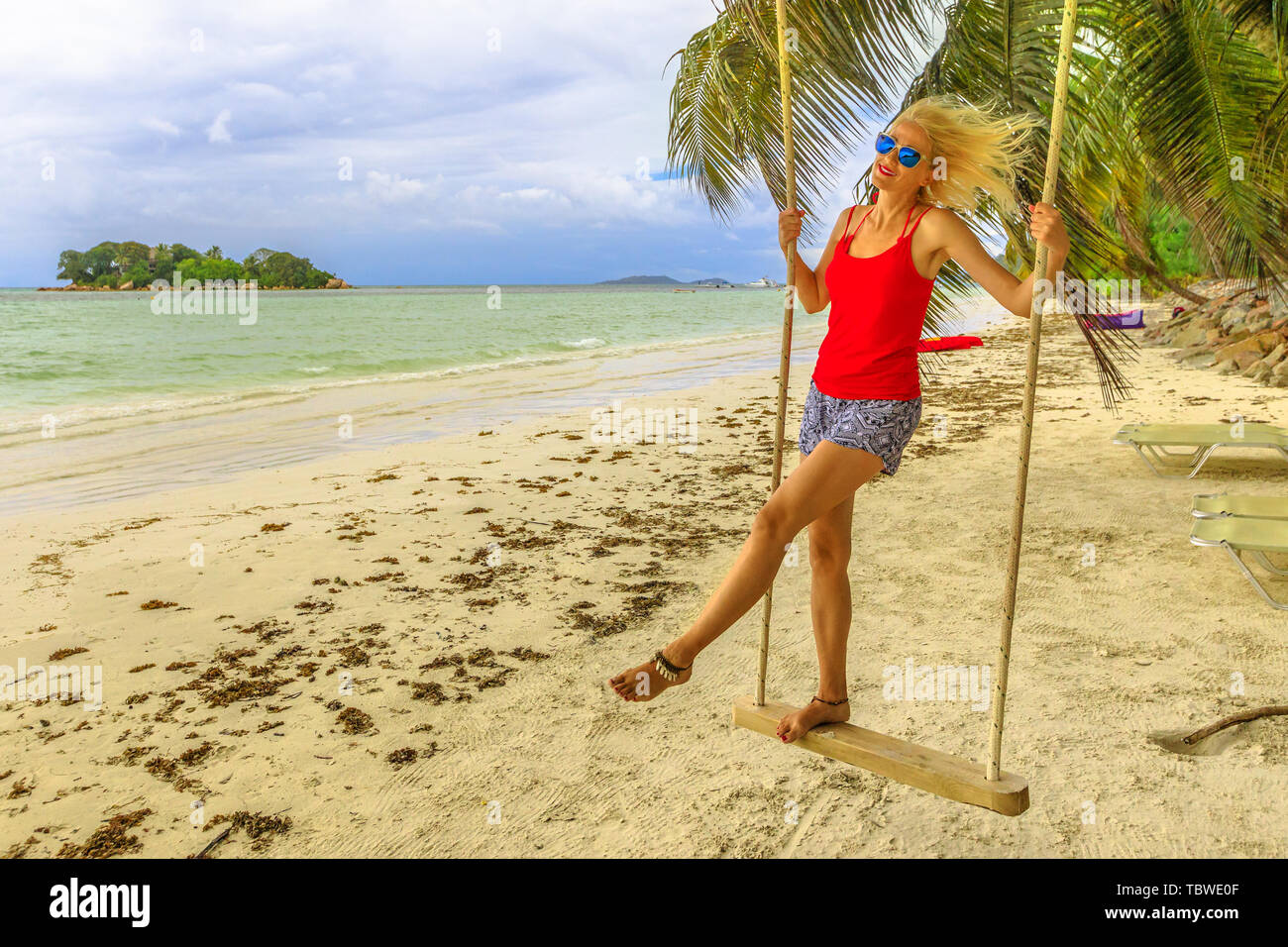 Carefree blonde woman swinging on tropical beach with palms of Anse Volbert Cote d'Or, Praslin, Seychelles, Indian Ocean. Islet of Chauve Souris on Stock Photo