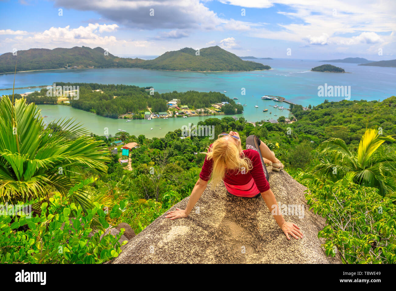 Tourist woman relaxing at lookout of Praslin after trekking inside Reserve of Fond Ferdinand. Scenic view from top view of Praslin on Bay of St. Anne - Stock Image