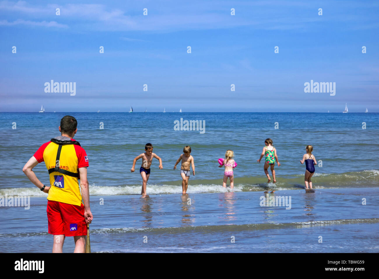 Belgian lifeguard watching over young children in bathing suits playing in the surf and jumping over the waves along the North Sea coast in summer - Stock Image