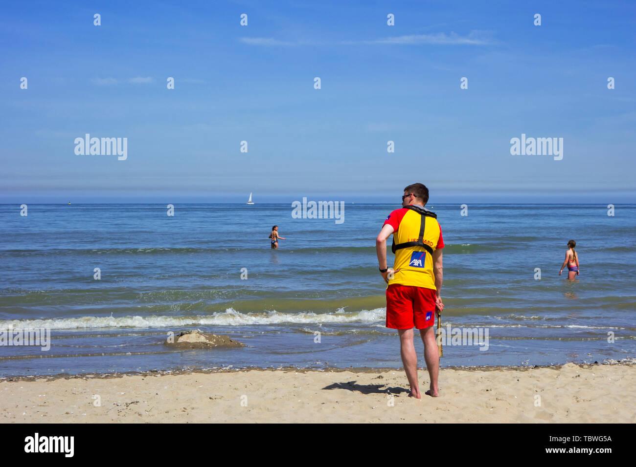 Beach lifeguard supervising bathers at seaside resort along the Belgian North Sea coast, Belgium - Stock Image