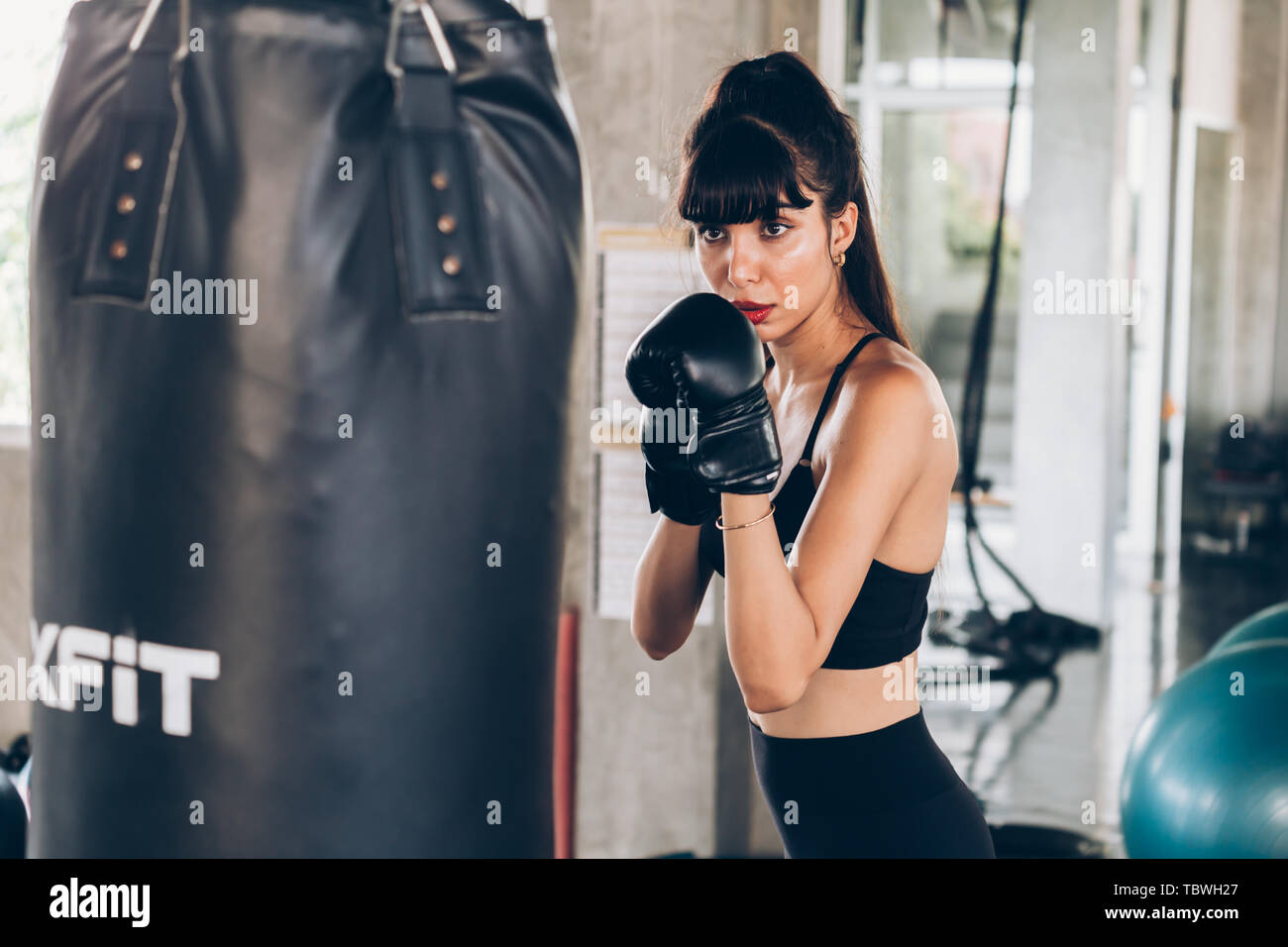 Slim Hispanic young female in sportswear punching boxing bag during training in modern gym - Stock Image