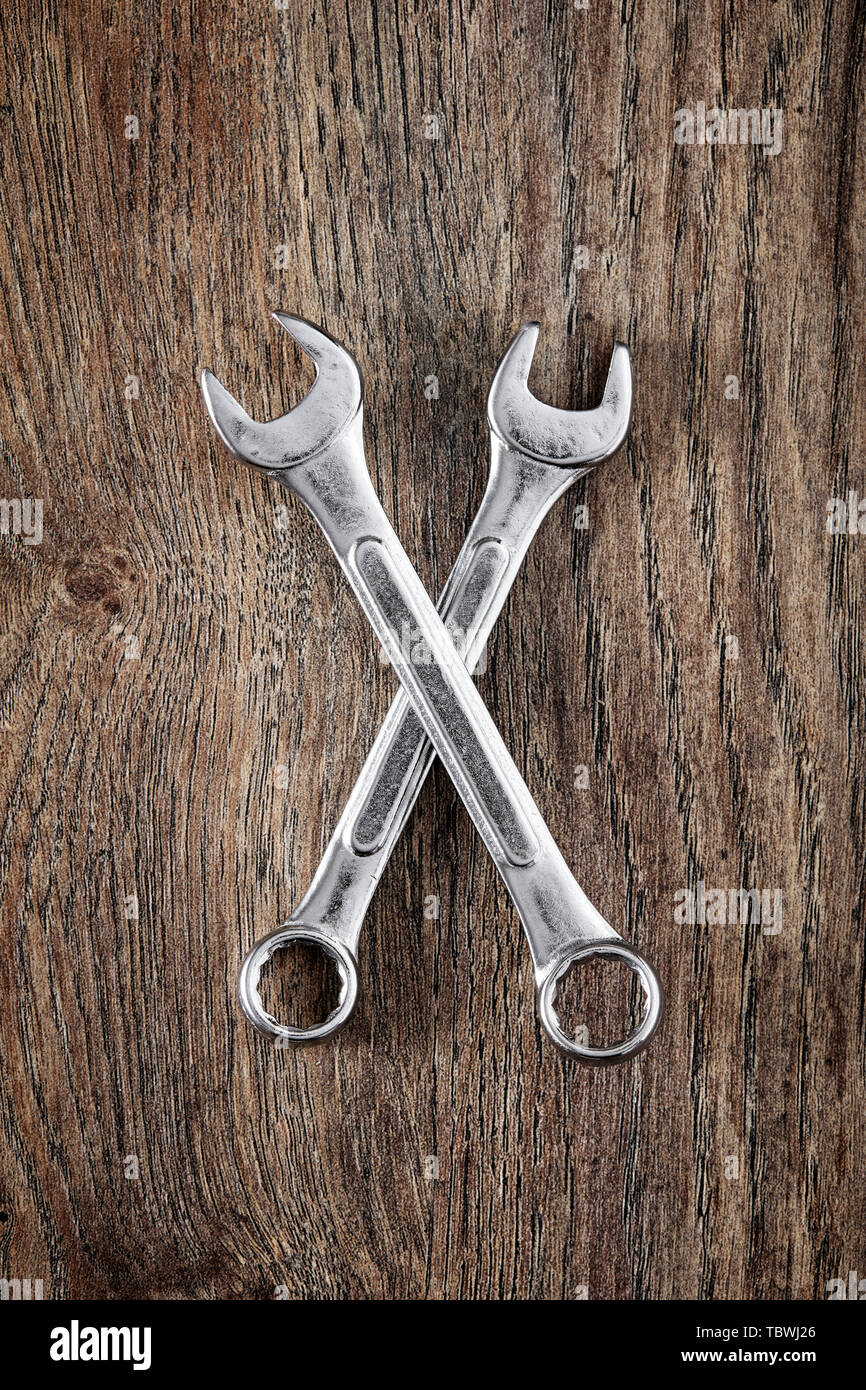 Two wrench crossed on wooden table. Close up top down view. - Stock Image