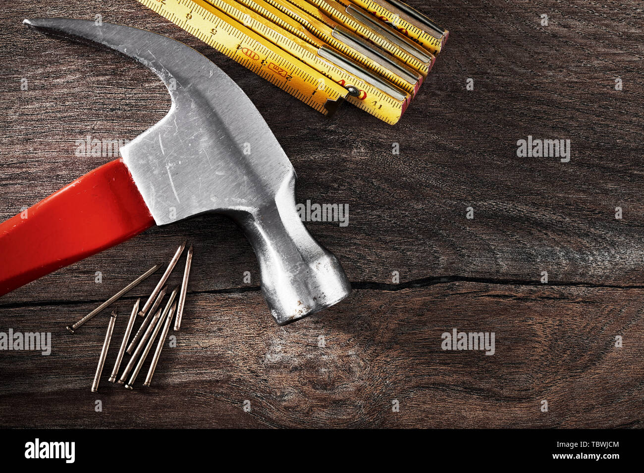 Hammer, folding rule and nails on vintage wooden table with copy space. Close up top down view. - Stock Image