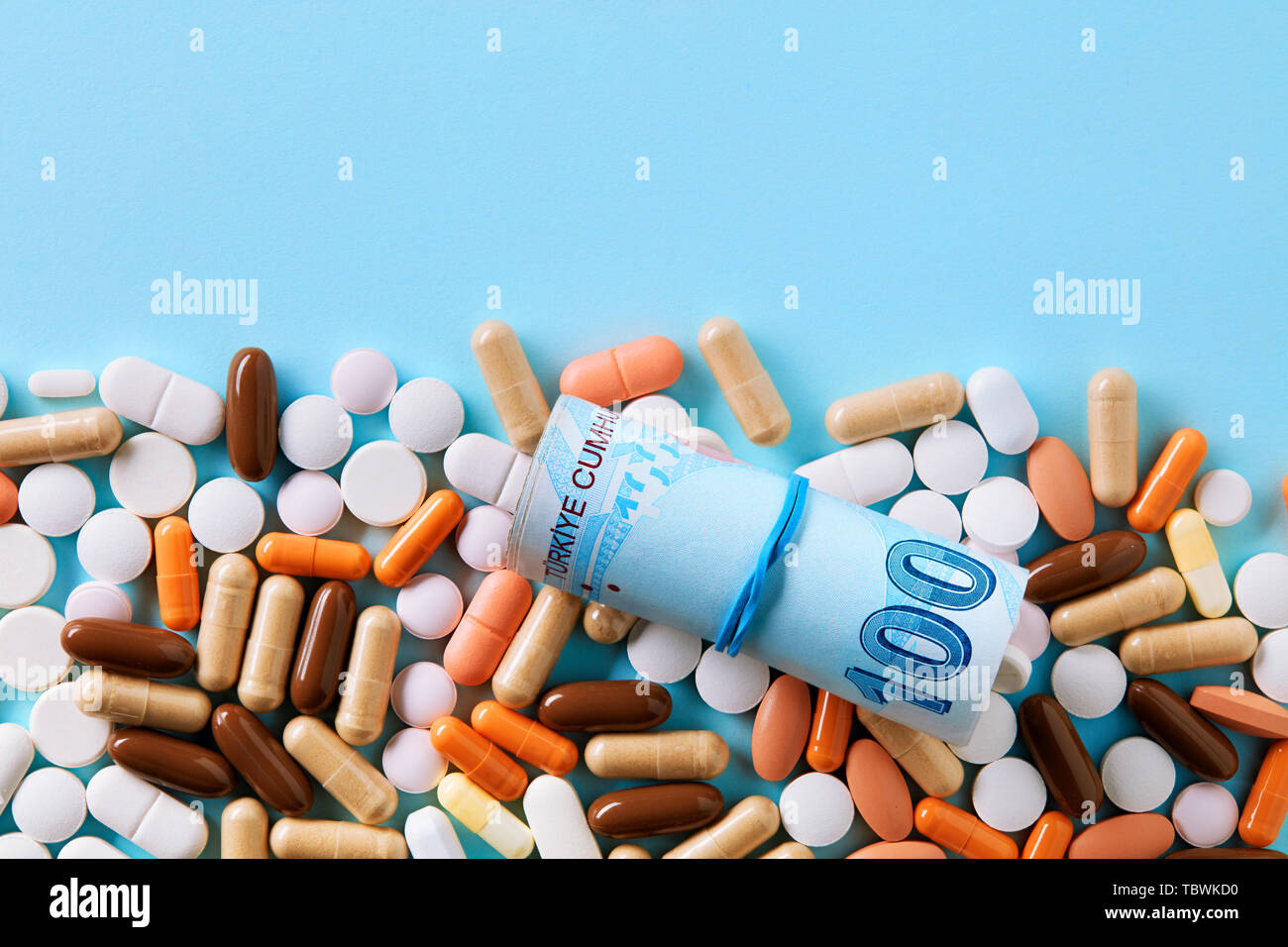 Hundred Turkish Lira bills over the medical pills. Expensive medicine and healthcare industry concept. Overhead macro view with copy space. Stock Photo