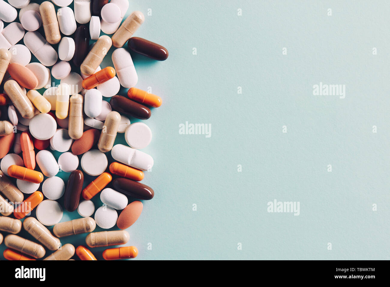 Heap of of colorful pills tablets and capsules with copy space for text. Top down view. Stock Photo