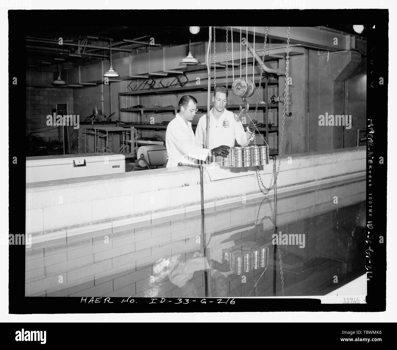 MTR BASEMENT. WORKERS (DON ALVORD AND CYRIL VAN ORDEN OF PHILLIPS PETROLEUM CO.) POSE FOR GAMMA IRRADIATION EXPERIMENT IN MTR CANAL. CANS OF FOOD WILL BE LOWERED TO CANAL BOTTOM, WHERE SPENT MTR FUEL ELEMENTS EMIT GAMMA RADIATION. INL NEGATIVE NO. 11746. Unknown Photographer, 8201954  Idaho National Engineering Laboratory, Test Reactor Area, Materials and Engineering Test Reactors, Scoville, Butte County, ID - Stock Image