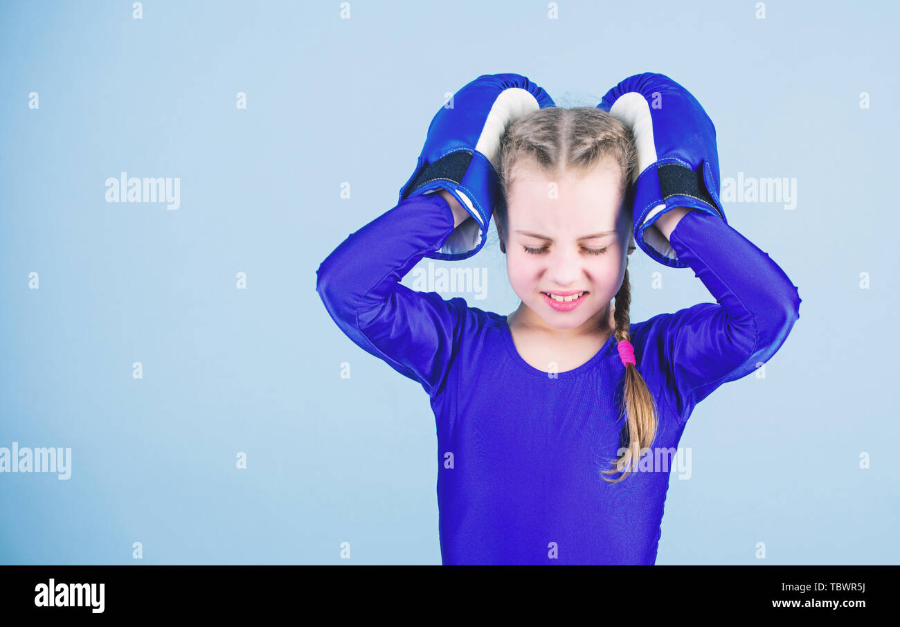 Risk of injury. Rise of women boxers. Girl cute boxer on blue background. With great power comes great responsibility. Boxer child in boxing gloves. Female boxer change attitudes within sport. - Stock Image