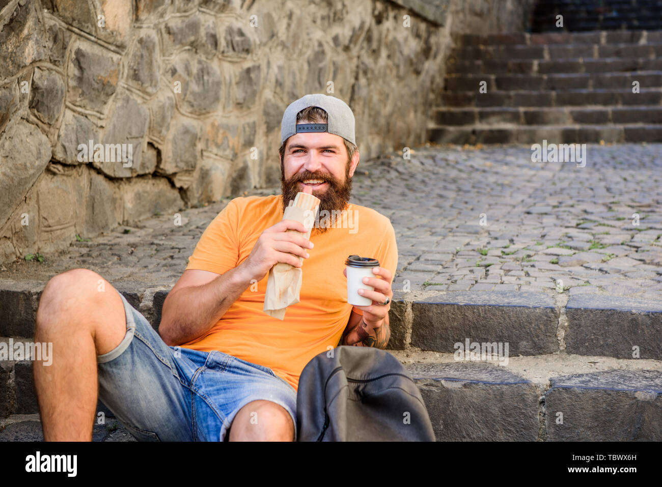 Hungry man snack. Junk food. Guy eating hot dog. Man bearded enjoy quick snack and drink paper cup. Street food so good. Urban lifestyle nutrition. Carefree hipster eat junk food while sit on stairs. - Stock Image