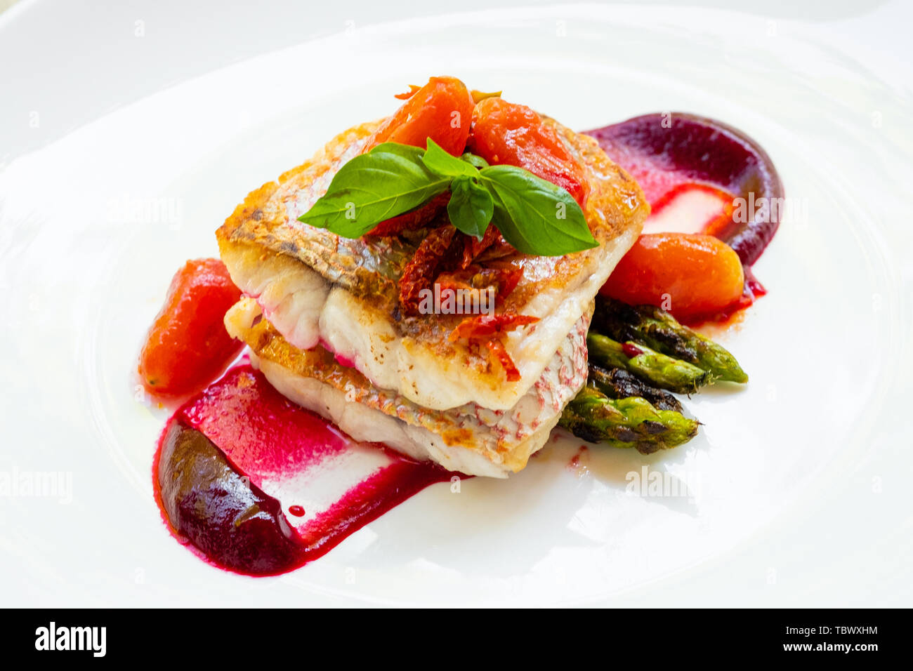 close up of a pan seared grilled red snapper fish fillet with asparagus, beetroot sauce,cherry san marzano tomatoes and basil on a white plate natural Stock Photo