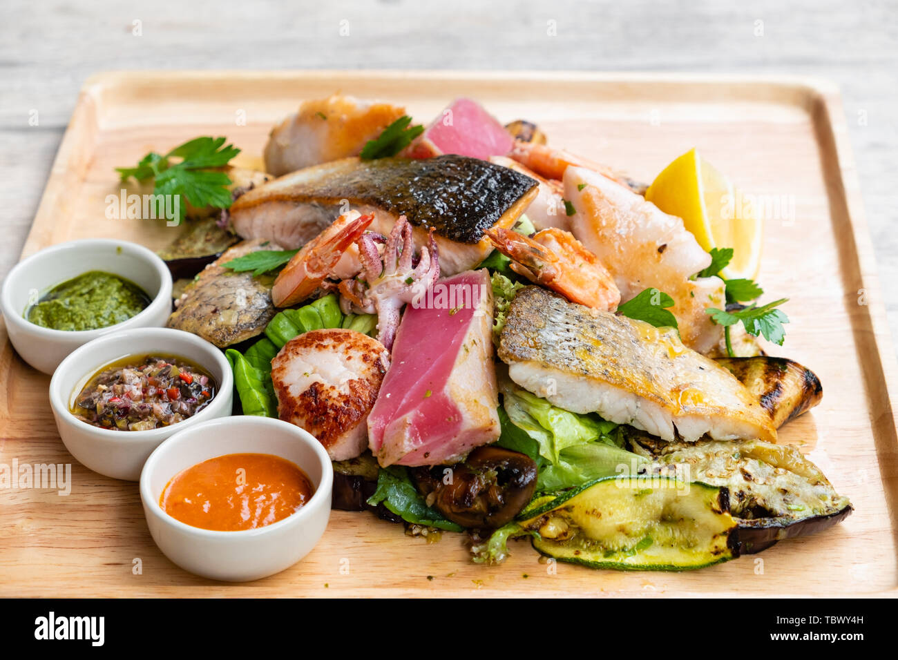 Close Up Of A Mixed Grilled Seafood And Fish Platter On A Wooden Board Salmon Tuna Calamari Scallop Prawn Clams Mussels Vegetable Lemon Spi Stock Photo Alamy