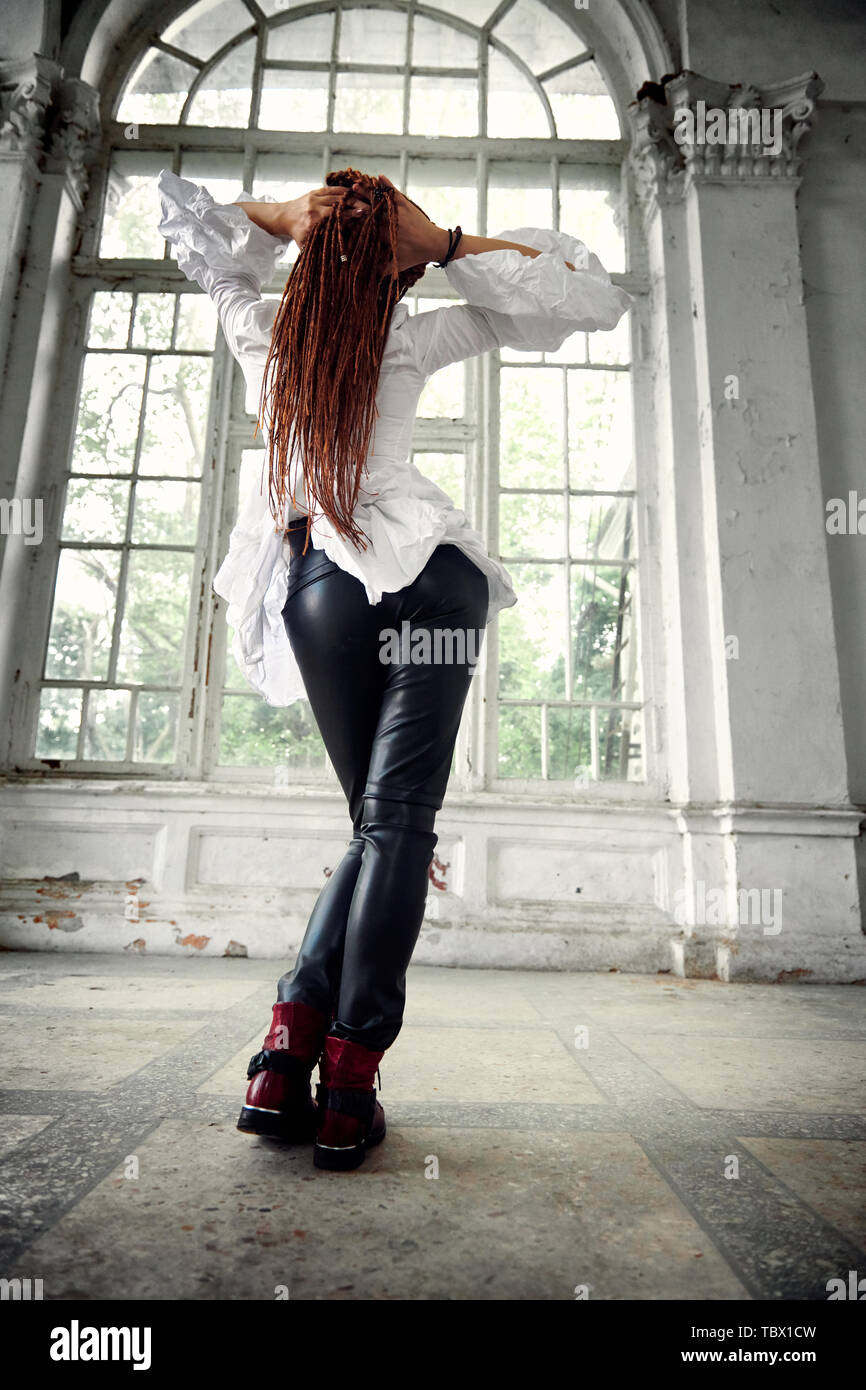 b337fe2bea3f9 dreadlocks fashionable girl dressed in white shirt and black leather  trousers posing in font of old