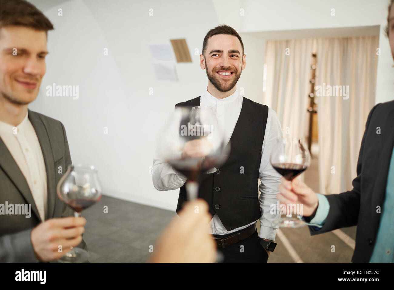 Portrait of professional sommeliers smiling happily and holding wine glasses, copy space Stock Photo