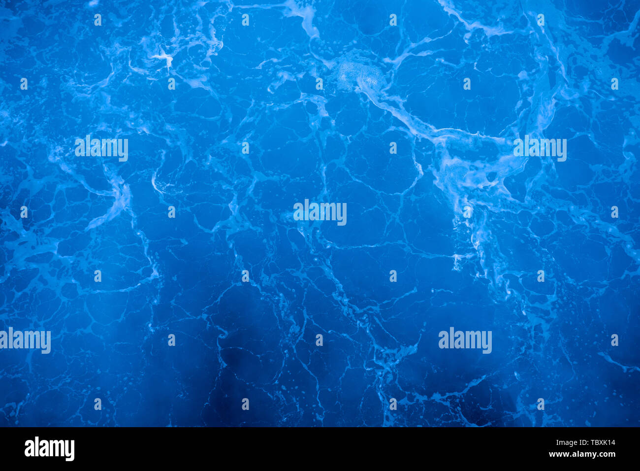 Dark blue deep sea surface, rippled water with sea foam and sparkling light - Stock Image