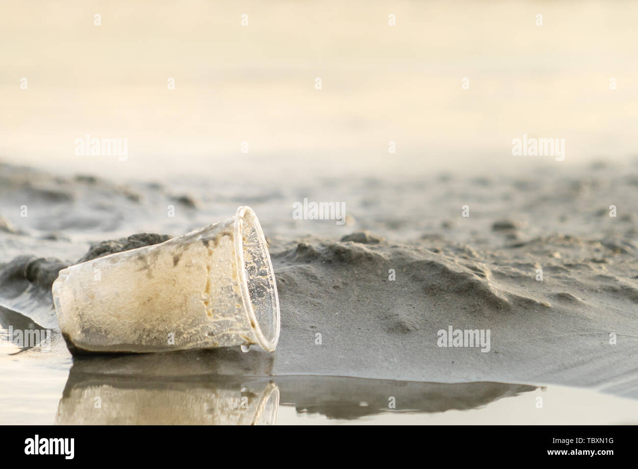 Rubbish Plastic cup left on the beach make pollution - Stock Image