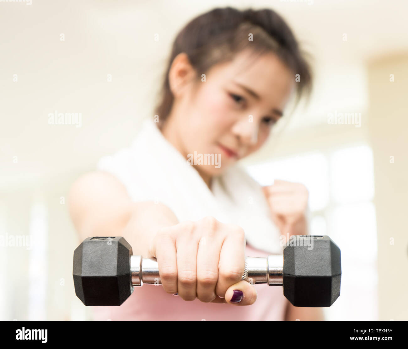 Asian woman is punching the Dumbbell forward in fitness - Stock Image