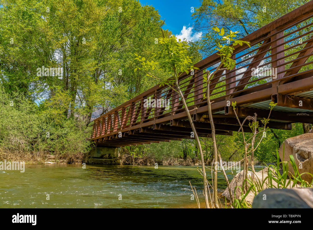 Bridge with metal guardrails over the glistening water at Ogden River Parkway - Stock Image