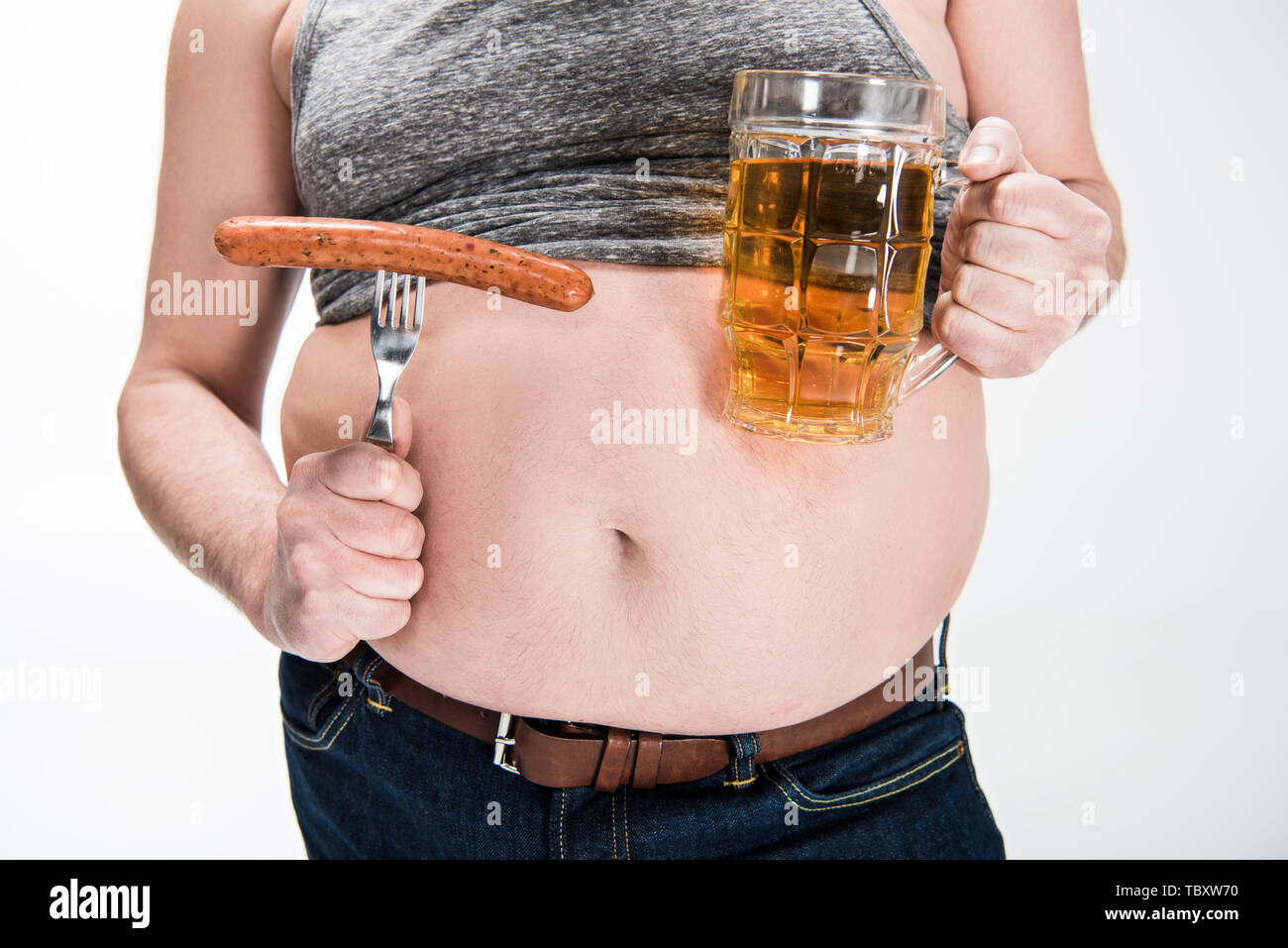 cropped view of overweight man showing belly and holding glass of beer with grilled sausage isolated on white Stock Photo