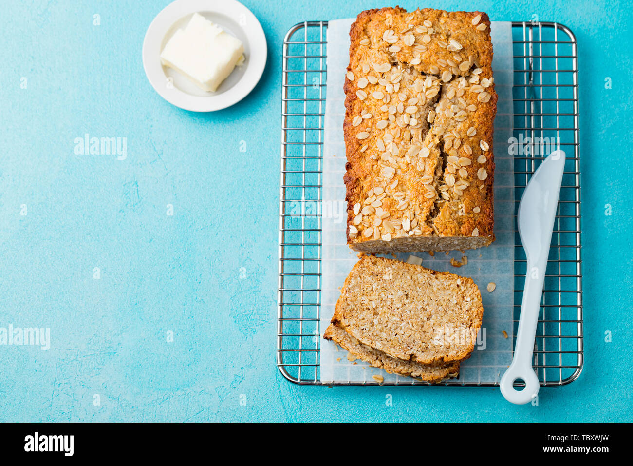 Healthy vegan oat, coconut loaf bread, cake on a cooling rack Blue background. Copy space. Top view. Stock Photo
