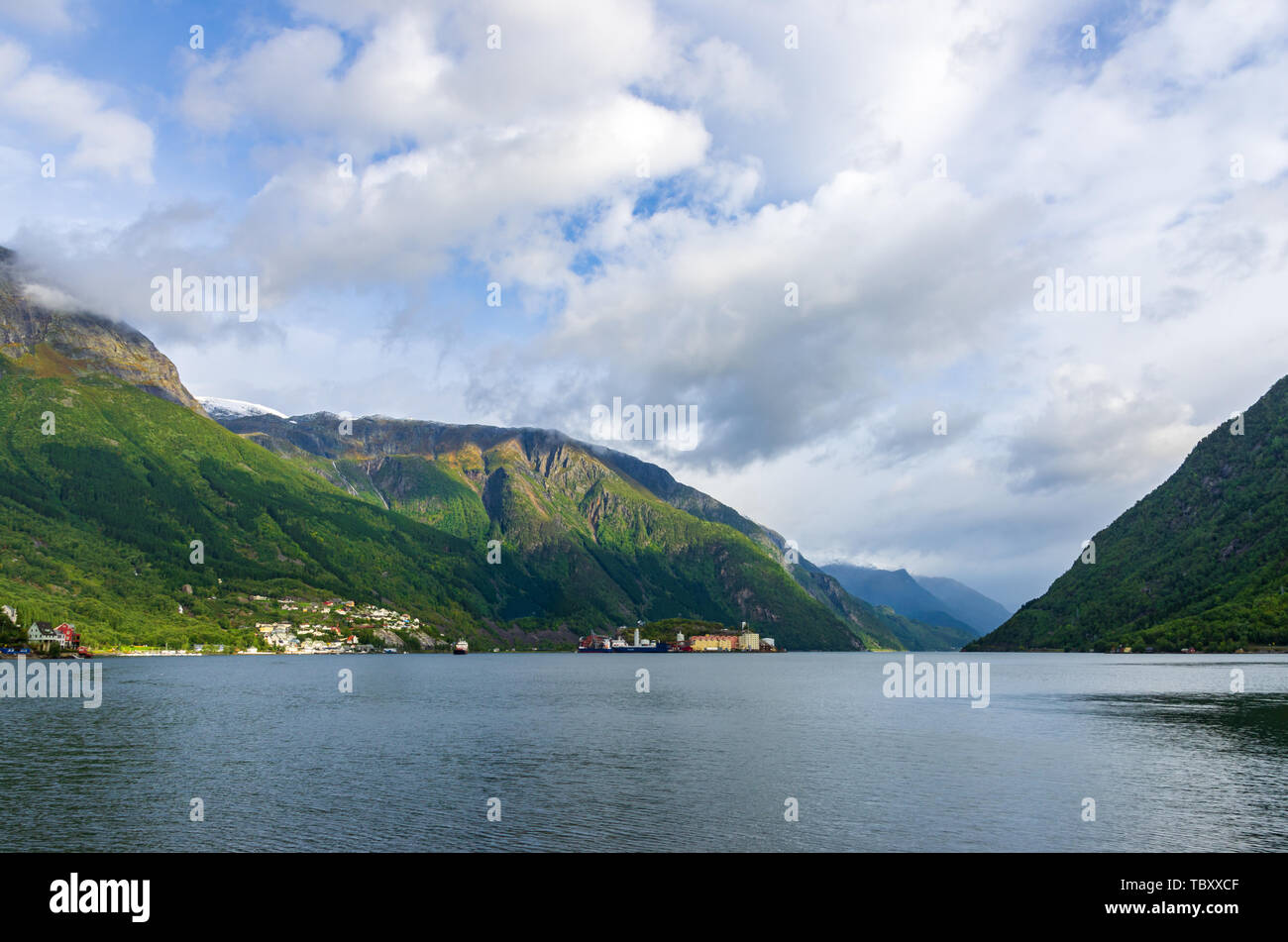Landscape of the Hardanger fjord seen from the village of Odda, with a factory in background - Stock Image