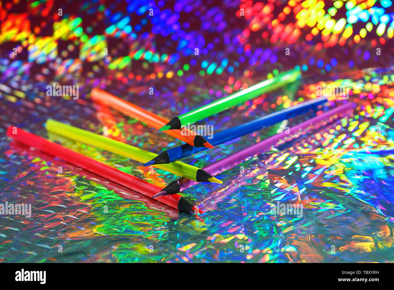 Back to school background with colorful neon color pencils on holographic foil backdrop. - Stock Image