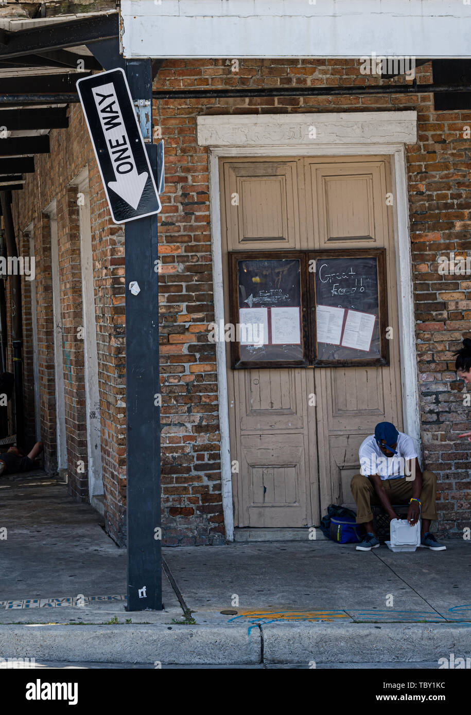 New Orleans, LA, USA -- May 23, 2019.  A Man sits in the doorway of an old Saloon;  a broken One Way sign points down. Stock Photo