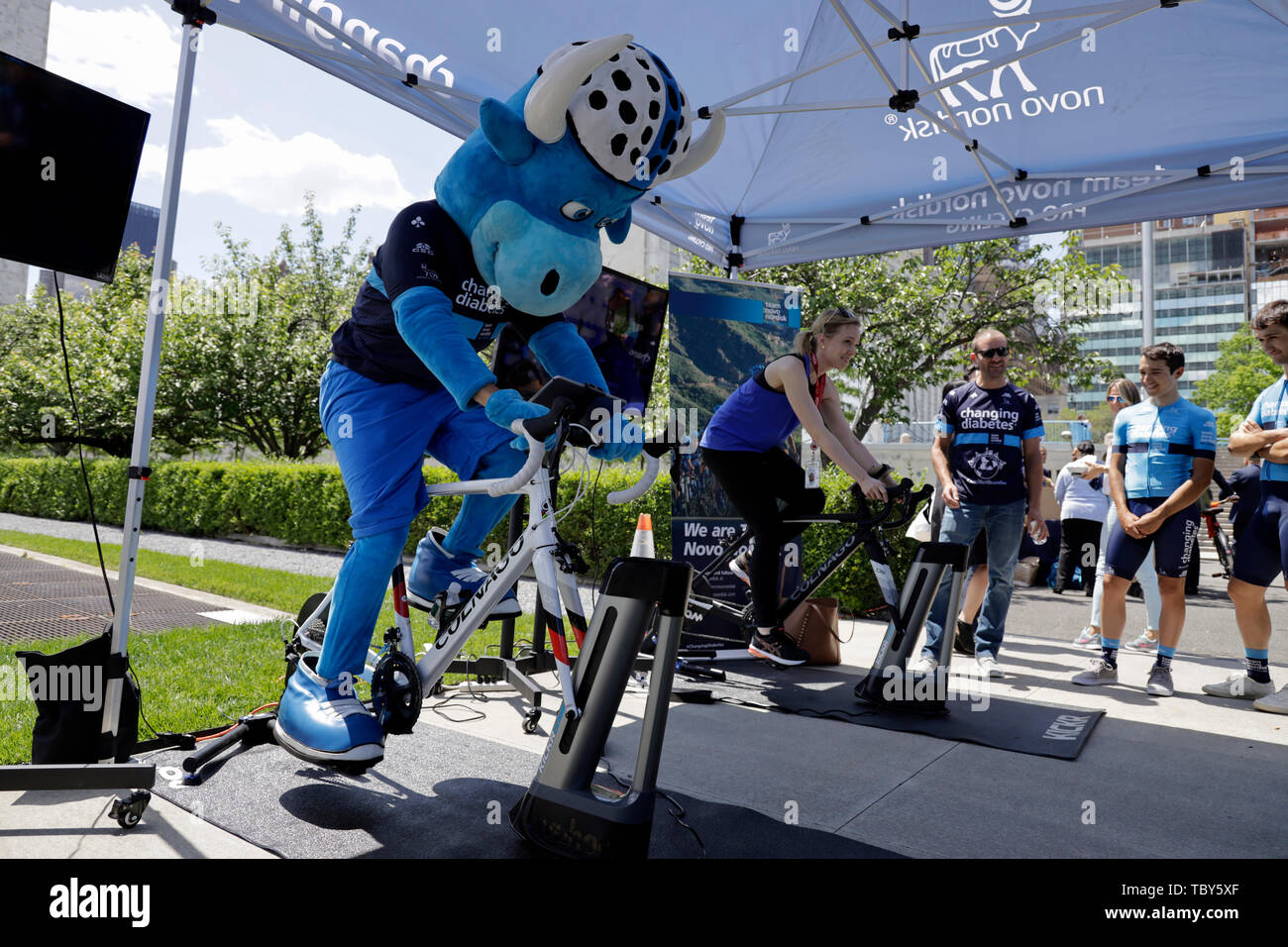 United Nations. 3rd June, 2019. A woman tries an indoor bike simulator during an event to commemorate the first World Bike Day at the UN headquarters in New York, June 3, 2019. The United Nations on Monday commemorated World Bicycle Day to acknowledge the uniqueness, longevity and versatility of bicycles. Credit: Li Muzi/Xinhua/Alamy Live News - Stock Image