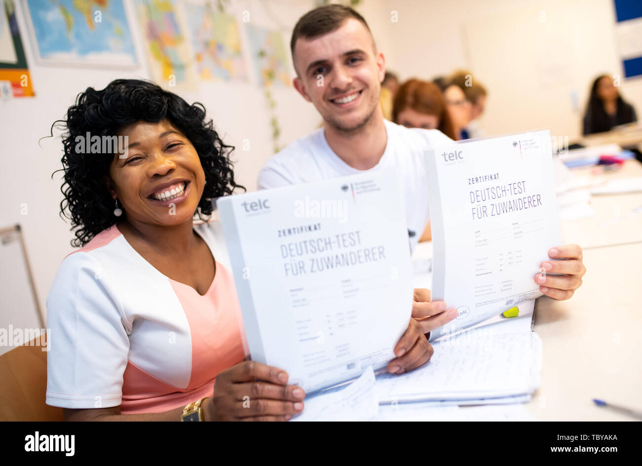 Munich, Germany. 04th June, 2019. Angela Nwaubani from Nigeria and Enver Latifi from Kosovo are happy about their certificates 'Deutsch-Test für Zuwanderer' (German test for immigrants) which they received for their successful participation in an integration course for immigrants of the Federal Office for Migration (BAMF). Credit: Sven Hoppe/dpa/Alamy Live News - Stock Image