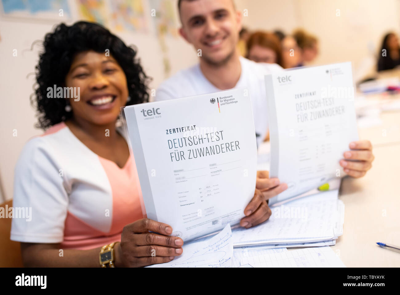 Munich, Germany. 04th June, 2019. Angela Nwaubani from Nigeria and Enver Latifi from Kosovo are happy about their certificates 'Deutsch-Test für Zuwanderer' (German test for immigrants) which they received for their successful participation in an integration course for immigrants of the Federal Office for Migration (BAMF). Credit: Sven Hoppe/dpa - ATTENTION: Names written out in the picture pixeled for legal reasons/dpa/Alamy Live News - Stock Image