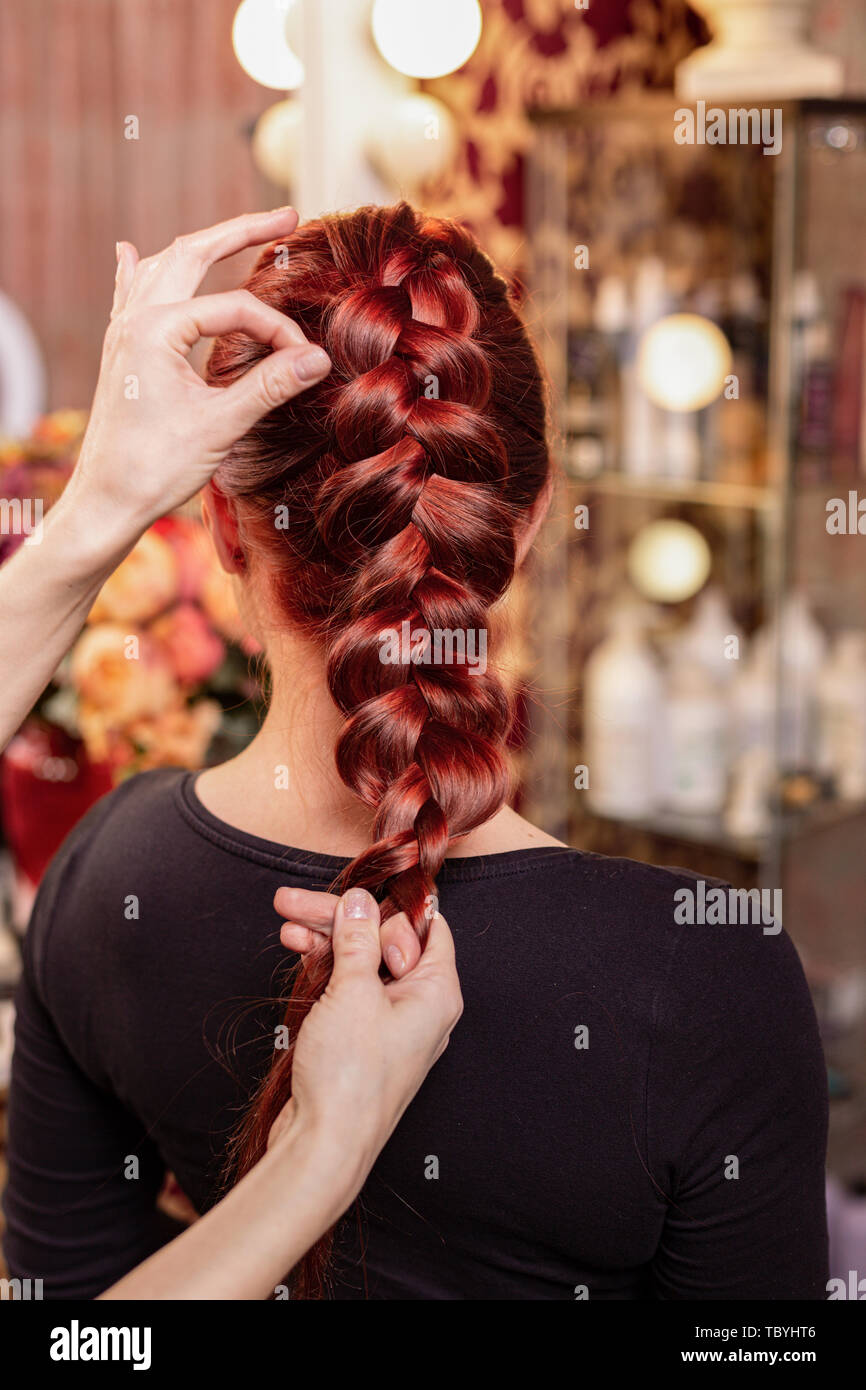 Beautiful, red-haired girl with long hair, hairdresser weaves a French braid, in a beauty salon. Professional hair care and creating hairstyles. - Stock Image