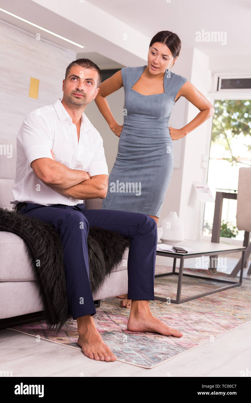 Offended young man sitting on sofa at home with disgruntled woman behind - Stock Image